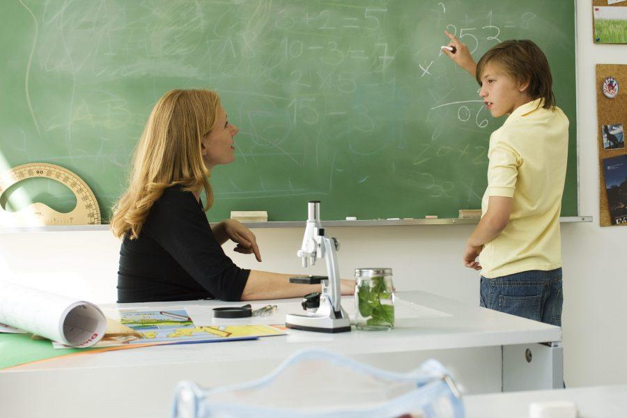 Schule, Junge an der Tafel mit Lehrerin