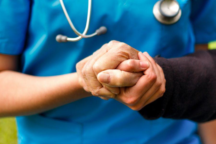 Pflegekraft hält Hand eines Patienten