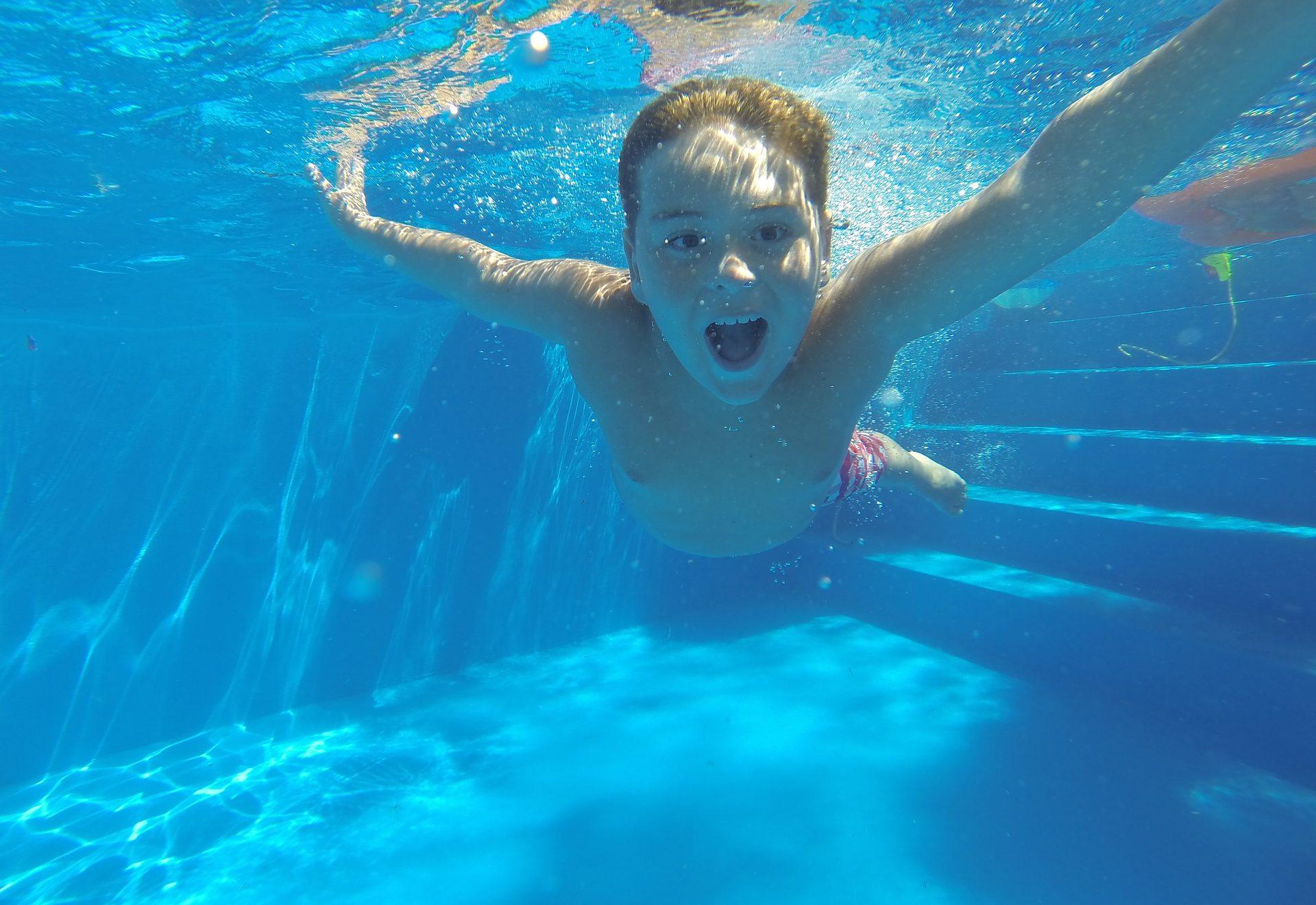 Kind taucht im Schwimmbad