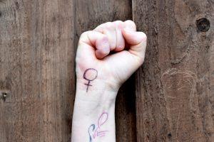 Die Faust einer Frau mit einem gemalten Venussymbol am Handgelenk