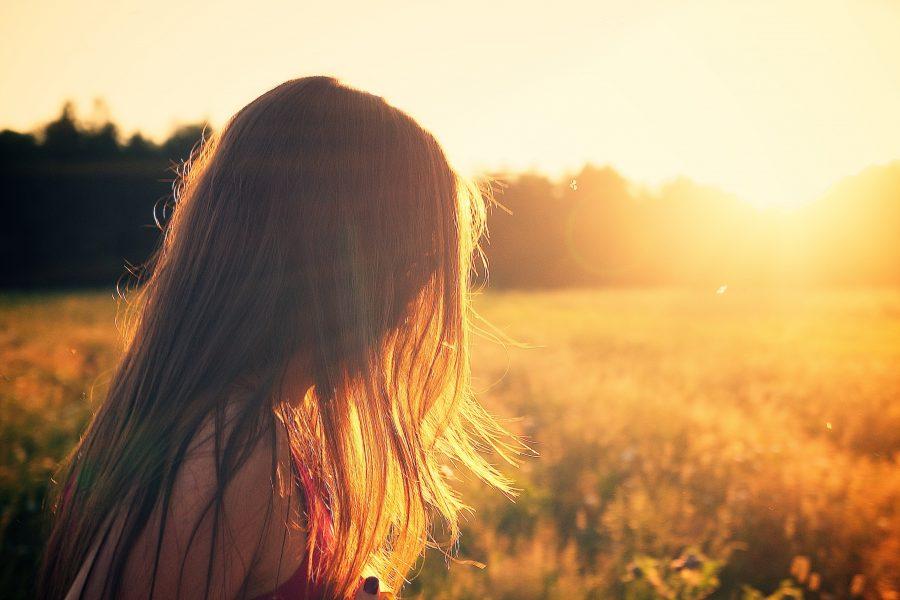Frau auf einem Feld im Sonnenuntergang