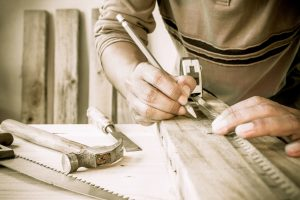 Mensch misst ein Stück Holz ab