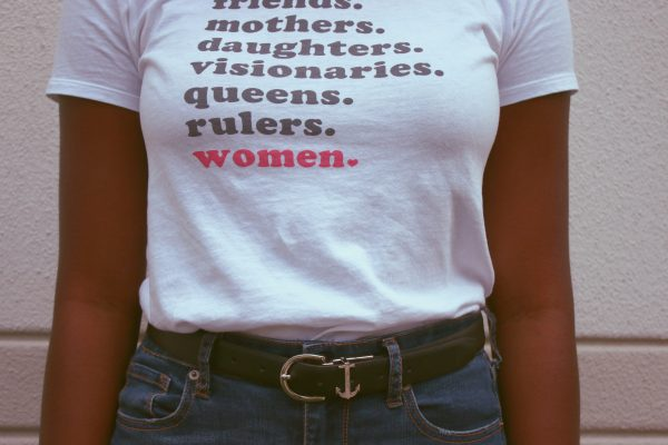 "Frau im T-Shirt mit Aufdruck: ""Friends. Mothers. Daughter. Visionaries. Queens. Rulers. Women."""