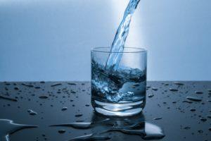 Wasser wird in ein Glas geschenkt