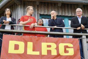 Serpil Midyatli, Olaf Scholz und Sönke Rix stehen beim DLRG auf dem Balkon und lassen sich die Funktionsweise des DLRG erklären.